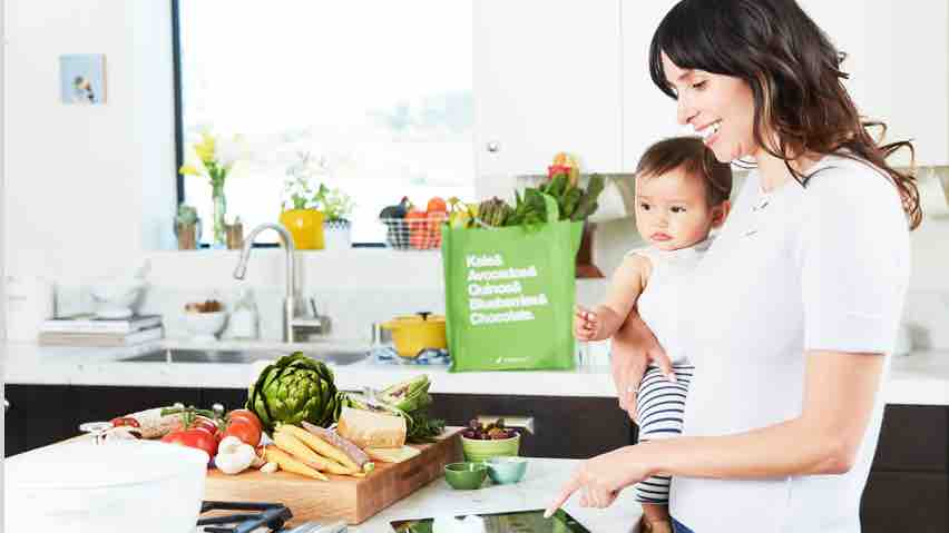 Woman holding a baby while reviewing her Instacart grocery order on a tablet with a countertop full of fresh produce