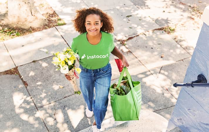 Instacart shopper on her way to deliver a bag of groceries and a bouquet of flowers